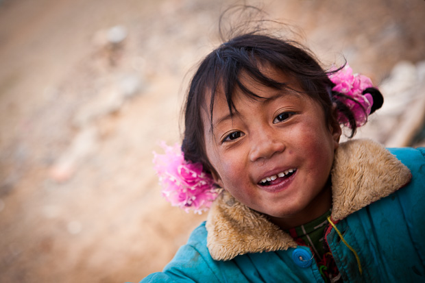 Laughing girl at temple, Maduo, Qinghai, Tibetan Plateau